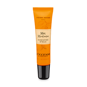 Tube of Honey Mandarin Lip Balm enriched with shea butter and a honey orange scent that softens lips.