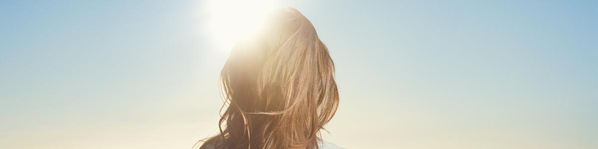 woman standing under the sun - L'Occitane